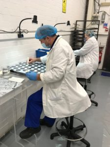 Two workers in white coats, hair covers and blue gloves inspect pieces of equipment in a clean room