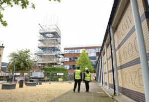 Two workers in hi vis jackets look over a site with scaffolding and a car park